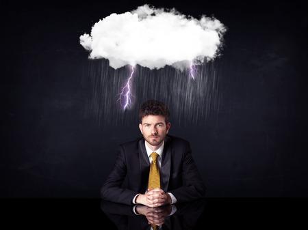 53337200 - depressed businessman sitting under a lightning rainy cloud