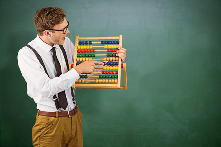 44598197 - geeky businessman using an abacus against green chalkboard